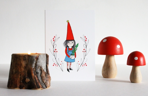 Christmas card with Nordic elf holding plant, photographed among wooden mushrooms and a tree stump candle holder