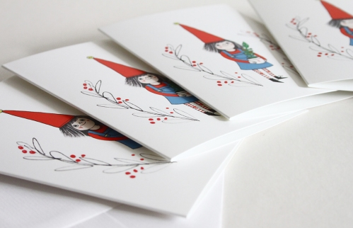 Christmas cards with same design, laid out on table.