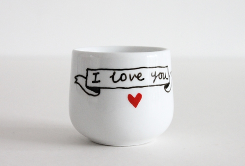 White egg cup with I love you written on the back in a ribbon banner, and a red heart.
