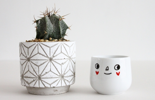 Egg cup with happy face and red heart cheeks, alongside a small cactus plant.
