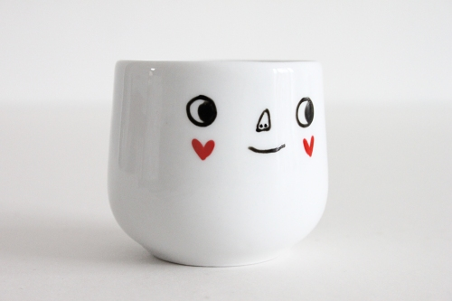 White egg cup with happy face and red heart cheeks drawn on.