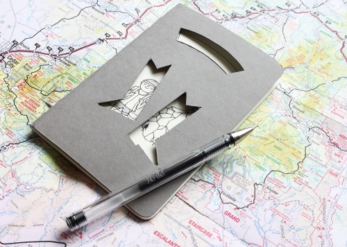 Grey Moleskine journal with cut-out walking boots revealing a hiker and mountain drawing.
