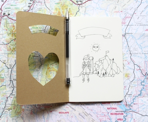 Hiker journal with pen on top of a map.