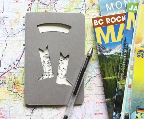 grey hiking journal with cut out boot shapes and cut out ribbon banner